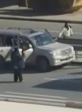 Dark-skinned persons loading arms into vehicle